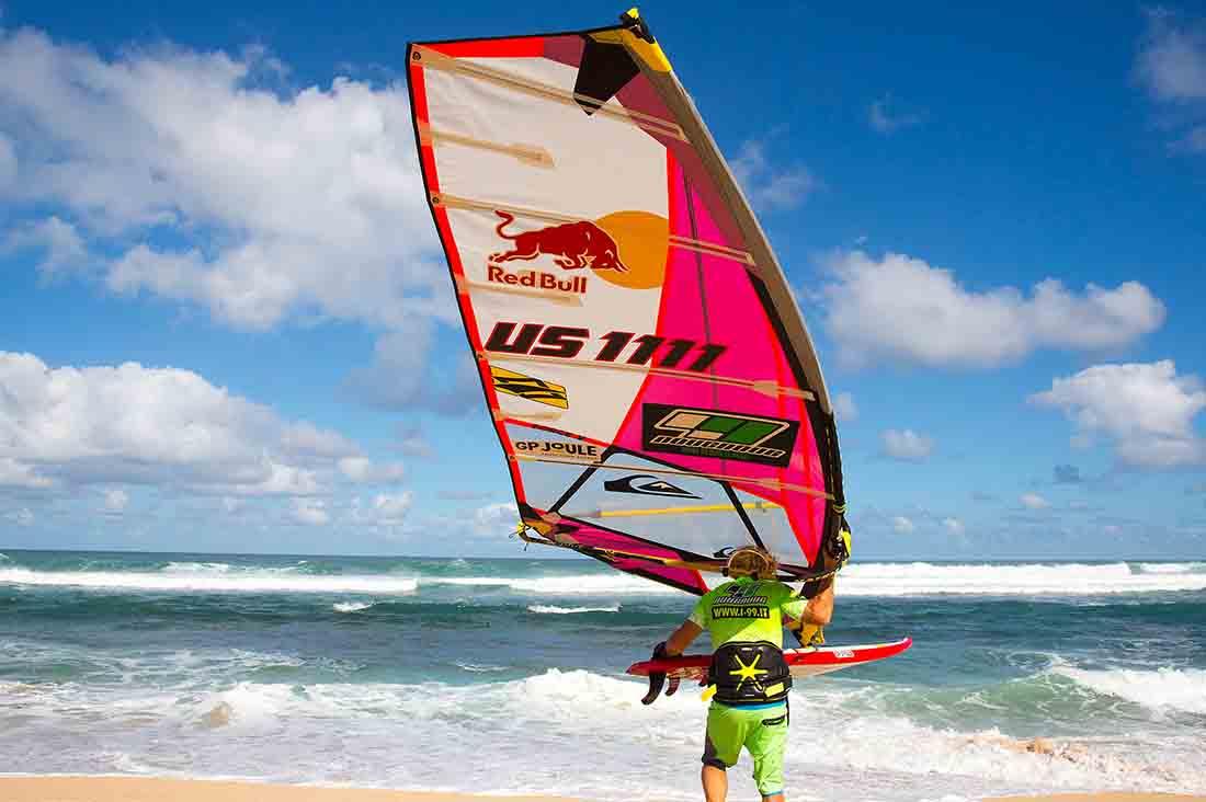 Robby Naish mit seiner Surf Ausrüstung am weg ins wasser