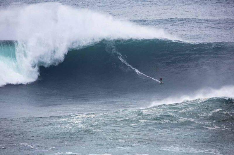 Ross Clarke Jones surft eine riesen Welle in Praia do Norte in Nazare Portugal